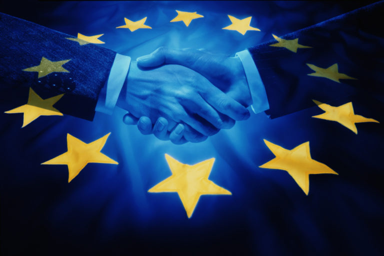 BLUE TONE IMAGE OF BUSINESS HANDSHAKE AGAINST EEC FLAG